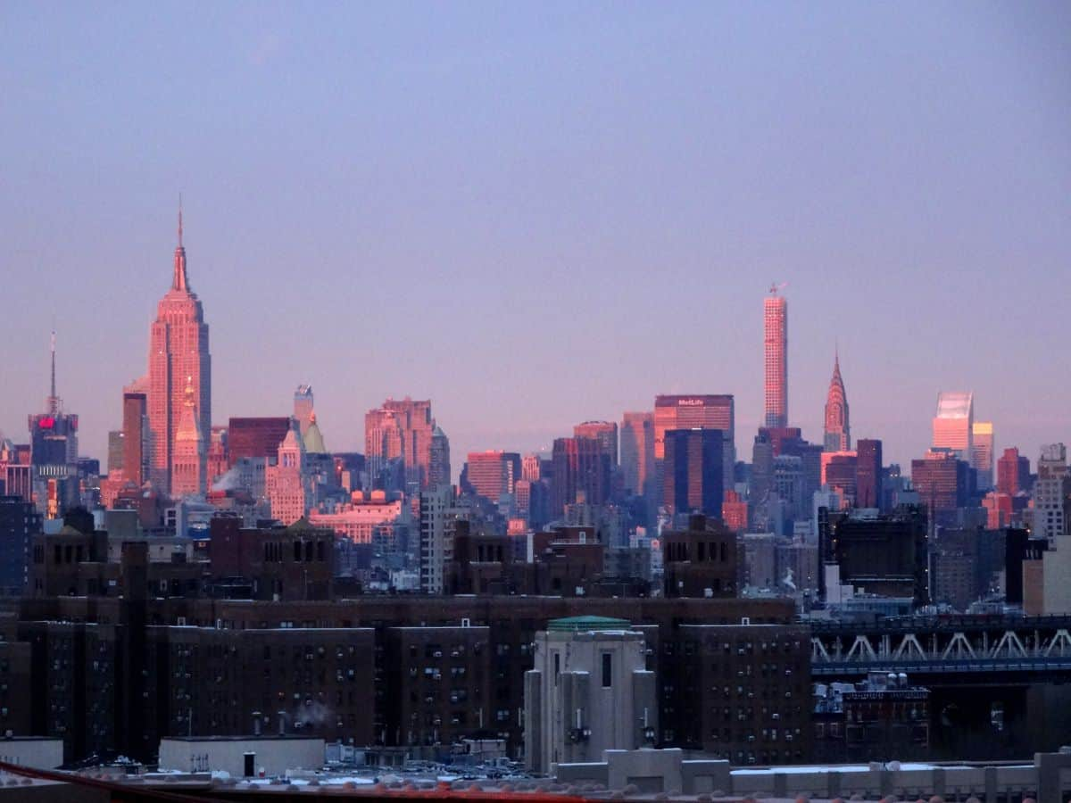 Brooklyn Bridge mit Ausblick auf die leuchtende Skyline von Manhattan im Sonnenuntergang
